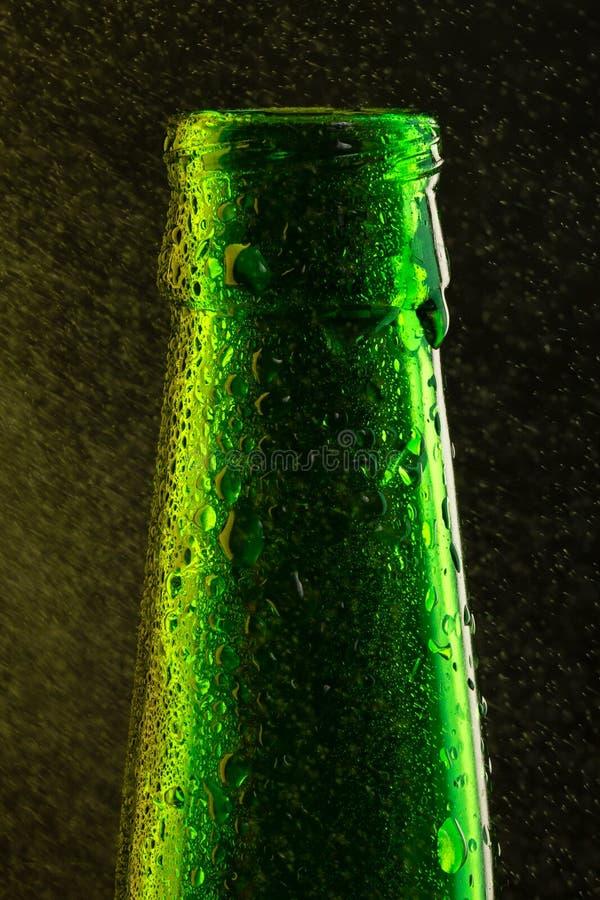 有下落的冰镇啤酒瓶在黑色 库存图片