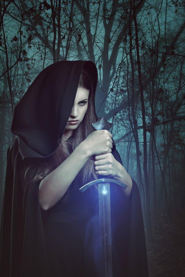 有不可思议的剑的美丽的妇女在一个黑暗的森林里 库存照片