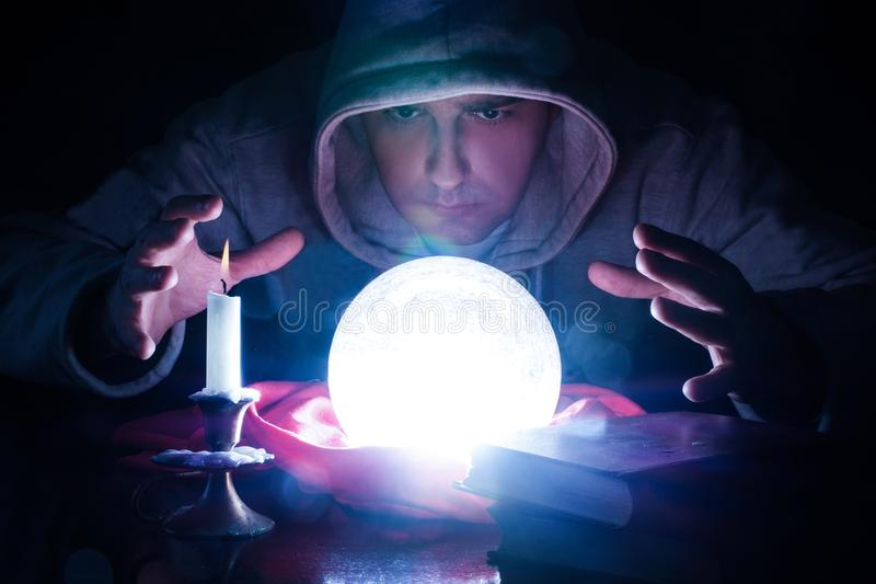 有不可思议的发光的天体的举行在一杯的巫术师和手光上 库存图片