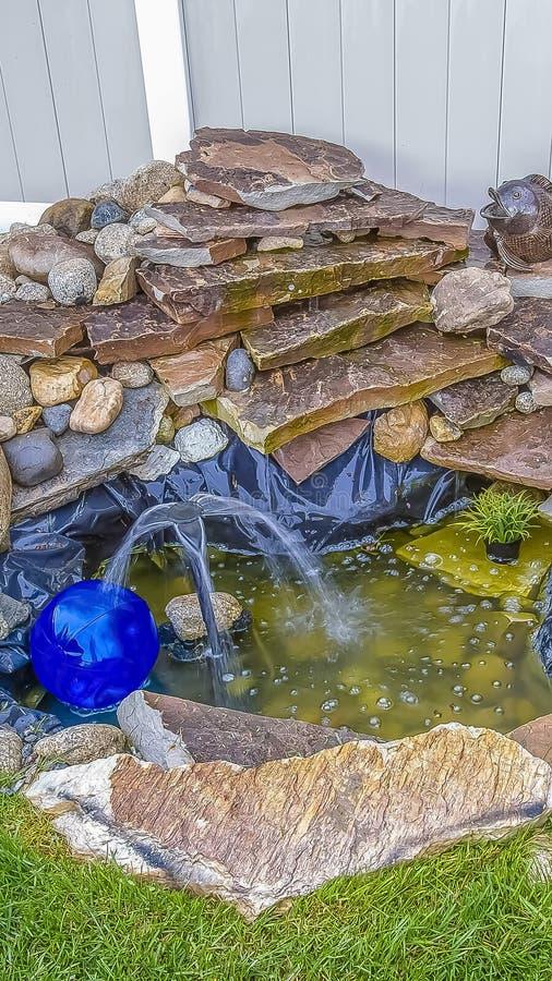 有不同的形状和大小岩石的垂直的喷泉在家的庭院 库存照片