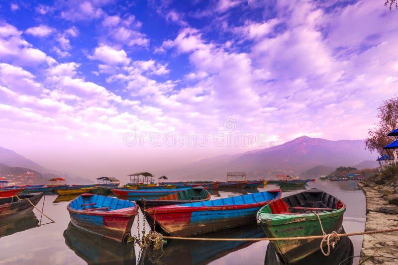 有不同颜色的令人惊讶的小船,天空反射在水中 库存照片