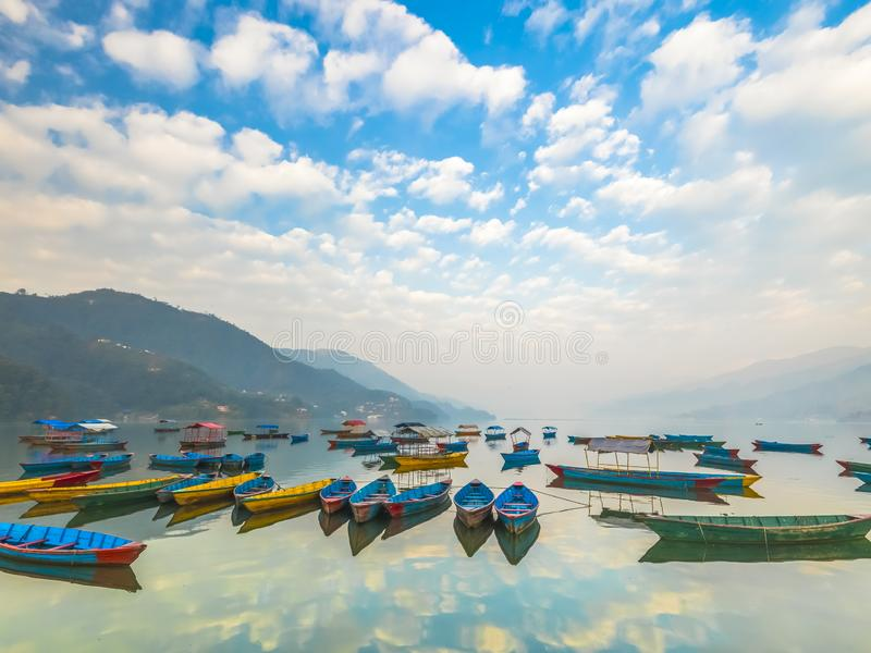 有不同颜色的小船,天空反射在水中 免版税库存照片