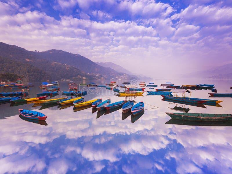 有不同颜色的尼泊尔小船,天空蔚蓝反射在水中 免版税库存照片