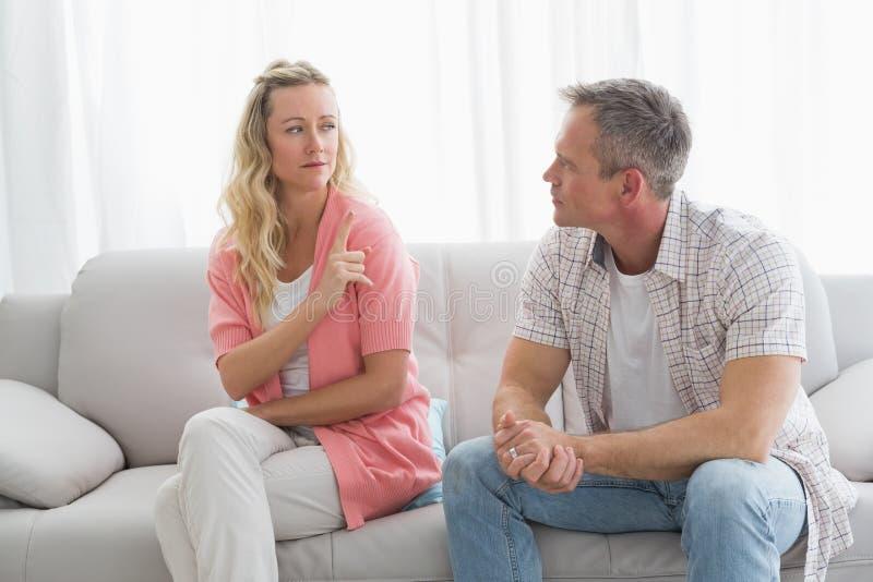 有不快乐的夫妇在长沙发的一个论据 库存照片