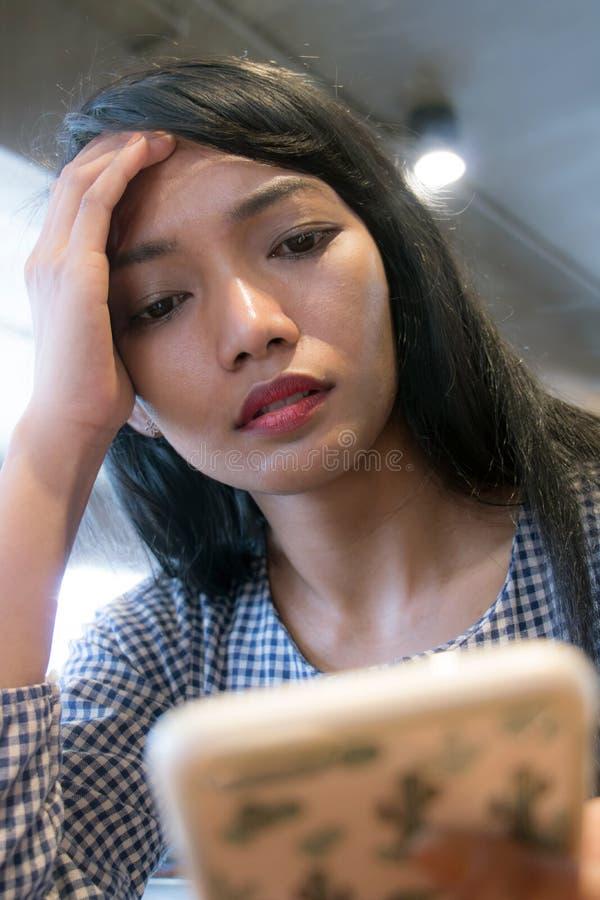 有不快乐的面孔的妇女调查她的电话 免版税库存图片