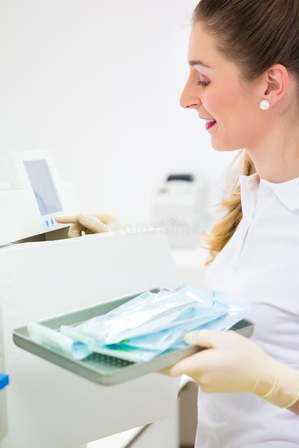 有不育的牙医工具的助理 库存图片