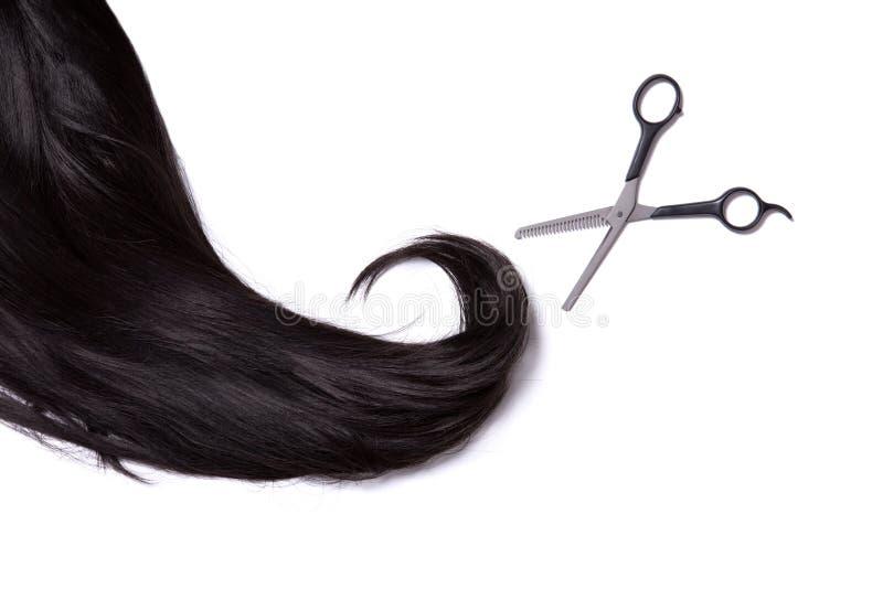 有专业剪刀的长的黑发光的头发 免版税图库摄影