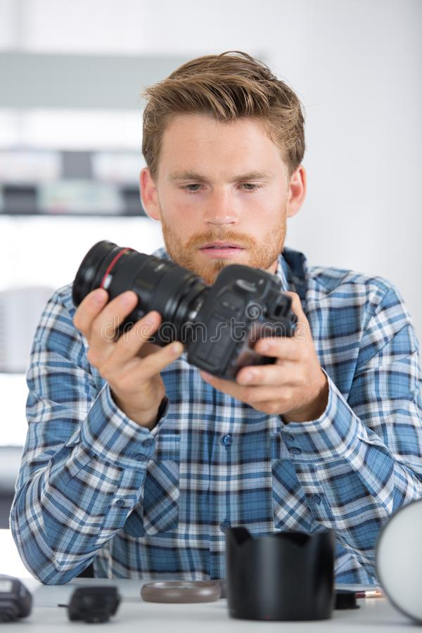 有专业数字照相机的年轻男性摄影师 免版税库存图片