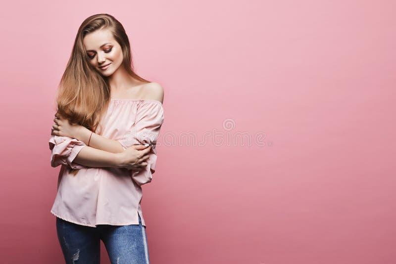 有专业明亮的构成的美丽和时兴的白肤金发的式样女孩在时兴的缎女衬衫和在蓝色牛仔裤 库存图片