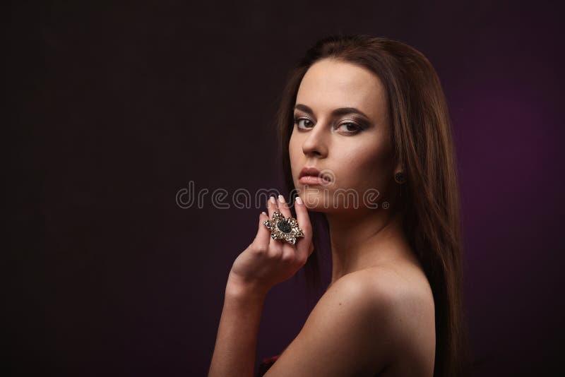 有专业显示大圆环和耳环的构成和发型的美丽的深色的妇女 给珠宝做广告 库存照片