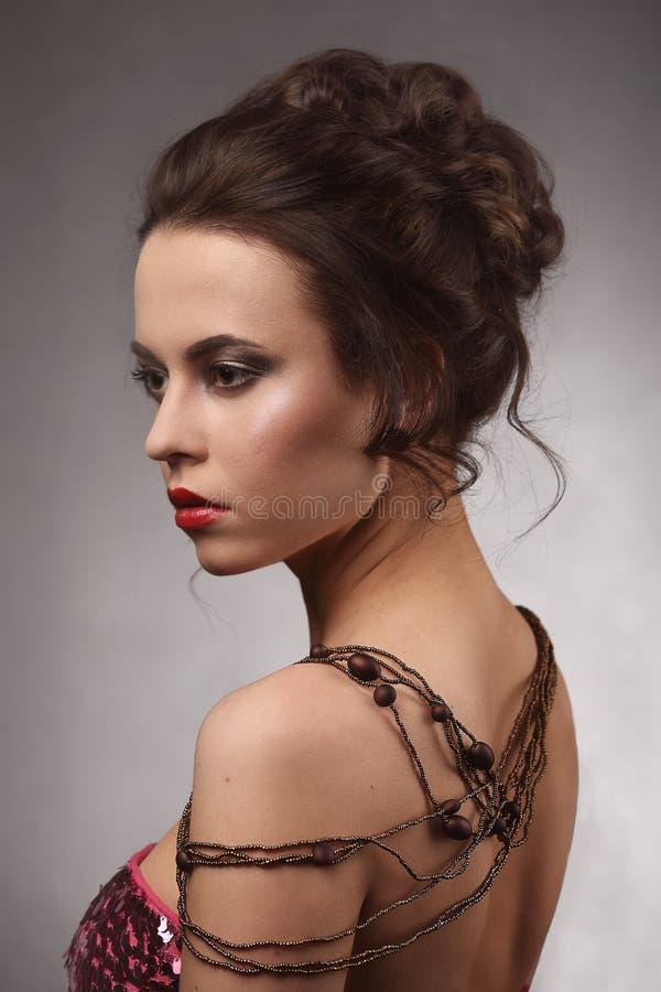 有专业构成和发型佩带的项链的美丽的深色的妇女在她的脖子和肩膀上 免版税库存图片