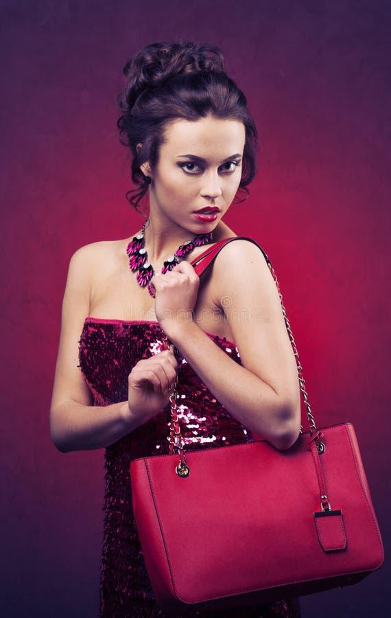 有专业构成和发型的美丽的深色的妇女与拿着桃红色提包的大项链 图库摄影