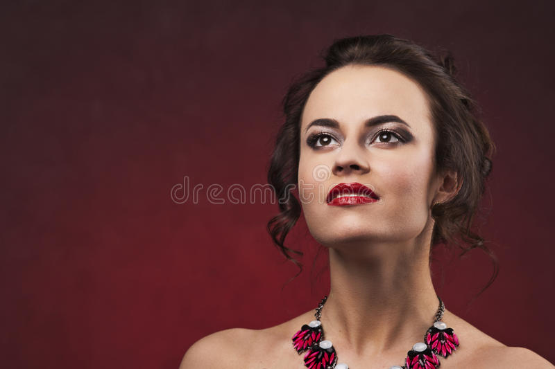 有专业构成和发型的美丽的深色的妇女与查寻大的项链 免版税库存照片