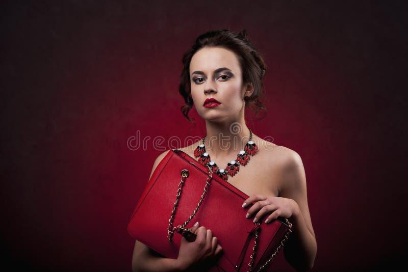 有专业构成和发型的美丽的深色的妇女与看对照相机的大项链拿着红色提包 库存图片