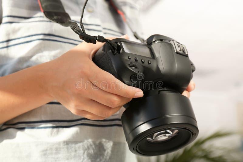 有专业照相机的女性摄影师在被弄脏的背景 免版税图库摄影