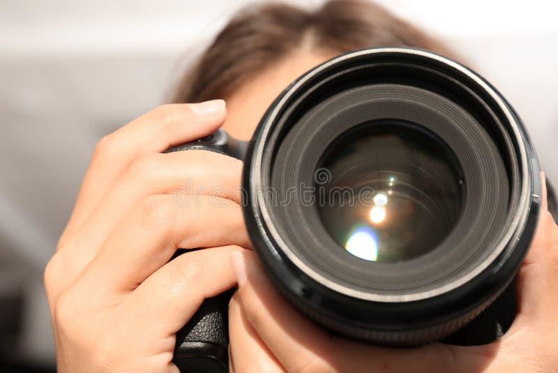 有专业照相机的女性摄影师在被弄脏的背景 库存图片