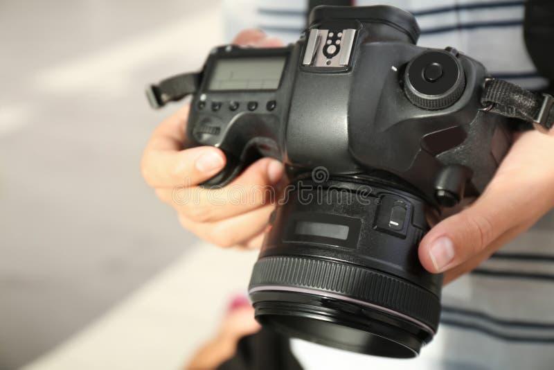 有专业照相机的女性摄影师在被弄脏的背景 免版税库存照片