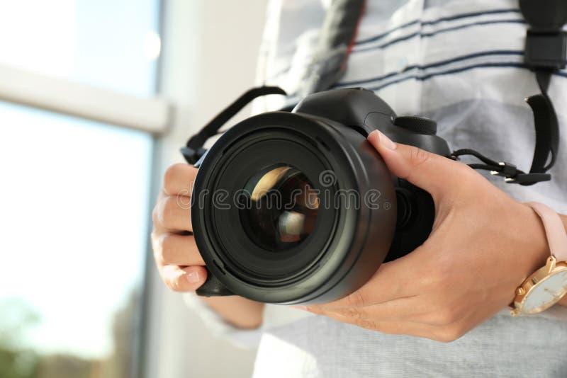 有专业照相机的女性摄影师在被弄脏的背景 库存照片