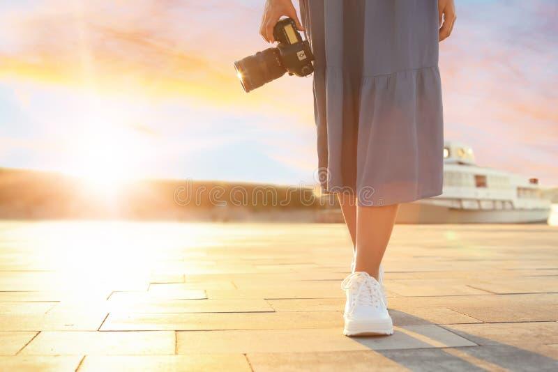 有专业照相机的年轻女性摄影师在日落点燃在码头 库存照片