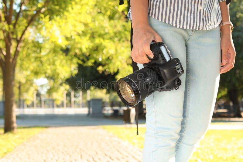 有专业照相机的年轻女性摄影师 图库摄影