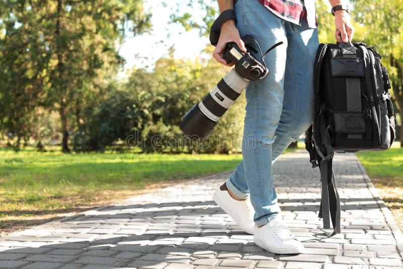有专业照相机的年轻男性摄影师 免版税库存图片