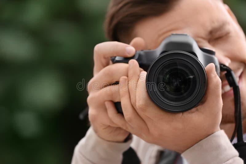 有专业照相机的男性摄影师在被弄脏的背景 免版税库存照片