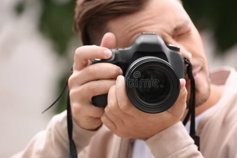 有专业照相机的男性摄影师在被弄脏的背景 库存图片