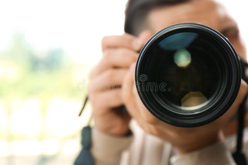 有专业照相机的男性摄影师在被弄脏的背景 免版税库存图片