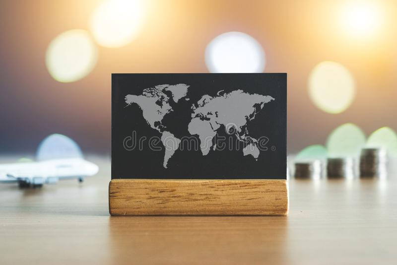 有世界地图的黑板与飞机和金钱在背景中铸造 旅行预算概念 旅行豪华概念 免版税图库摄影