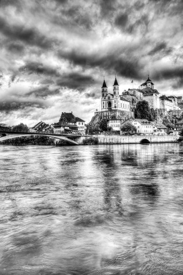 有世袭的社会等级的Aarburg村庄和教会和河与小船的Aare在前景 免版税图库摄影