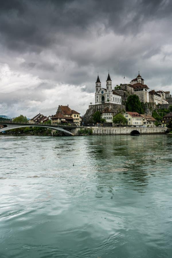 有世袭的社会等级的Aarburg村庄和教会和河与小船的Aare在前景 免版税库存照片