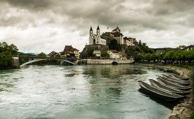 有世袭的社会等级的Aarburg村庄和教会和河与小船的Aare在前景 库存照片