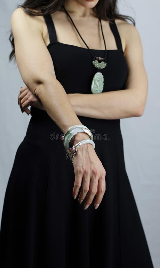 有东方玉首饰的妇女 镯子和垂饰与被雕刻的绿色玉石头 库存图片