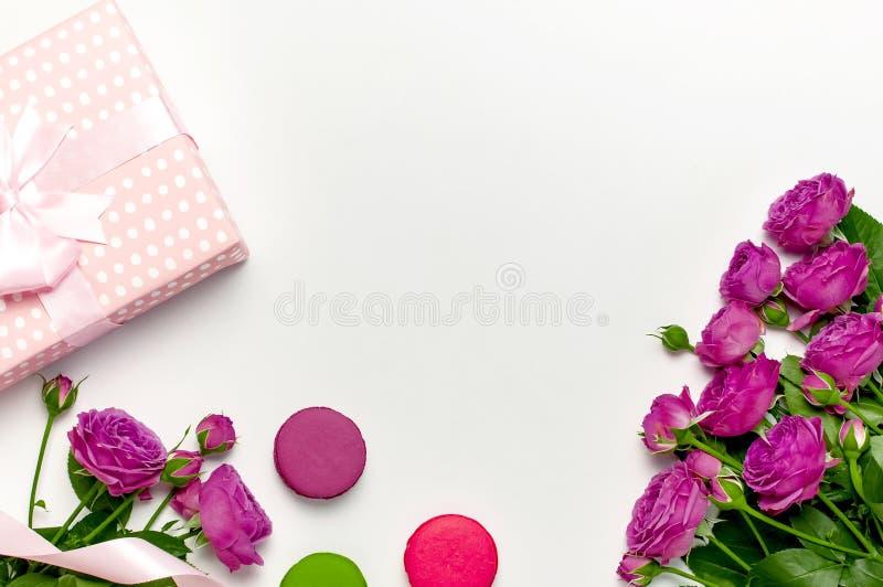 有丝带、明亮的桃红色玫瑰、蛋糕macaron或者蛋白杏仁饼干的礼物盒在浅灰色的背景 r 免版税库存照片