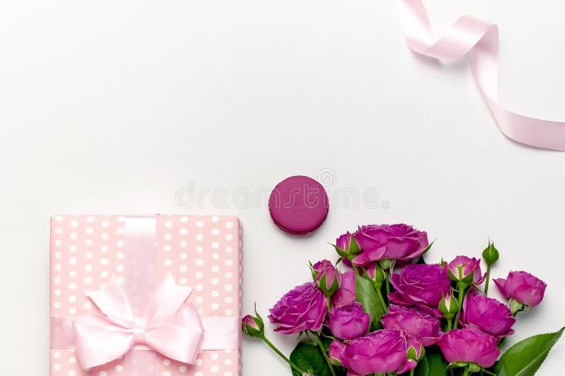 有丝带、明亮的桃红色玫瑰、蛋糕macaron或者蛋白杏仁饼干的礼物盒在浅灰色的背景 r 免版税库存图片