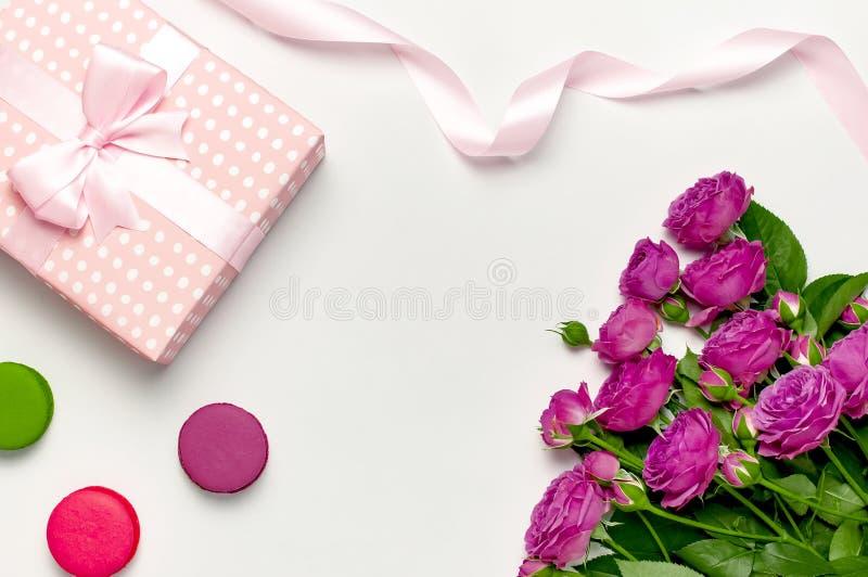 有丝带、明亮的桃红色玫瑰、蛋糕macaron或者蛋白杏仁饼干的礼物盒在浅灰色的背景 r 图库摄影