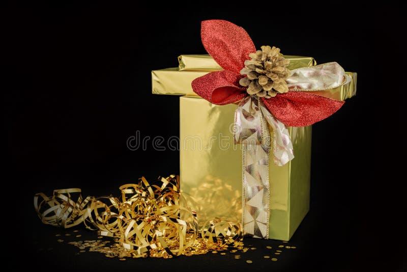有丝带、芦苇领带和金黄杉木锥体的一个金黄被包裹的礼物盒在黑背景中 库存照片