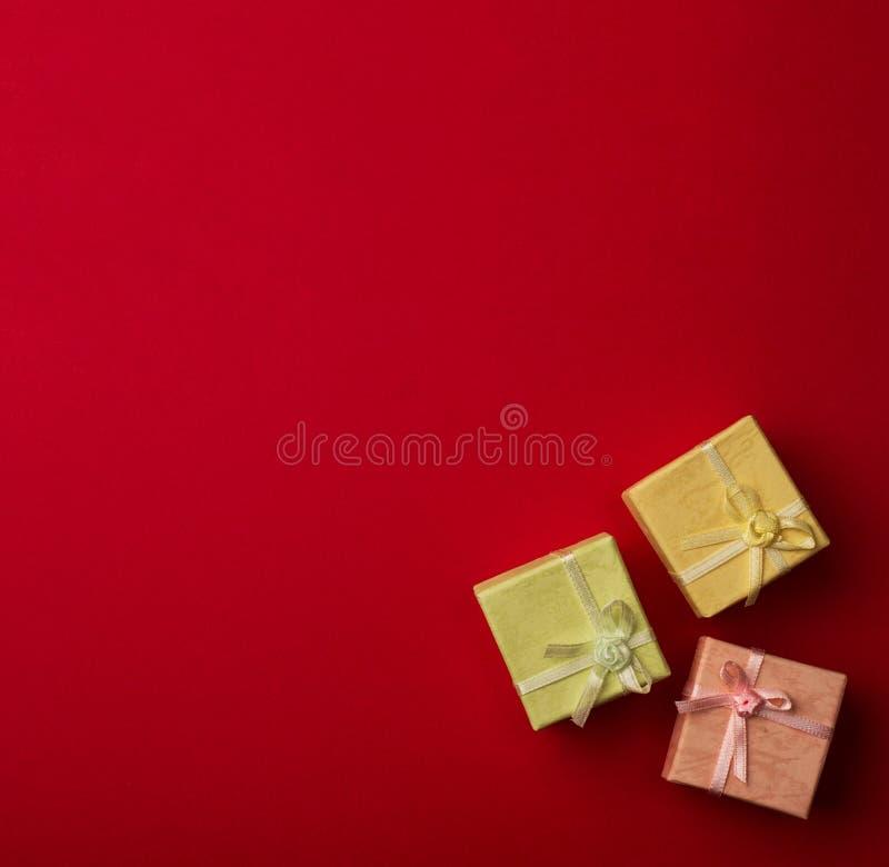 有丝带的三个小礼物盒在红色背景 库存图片