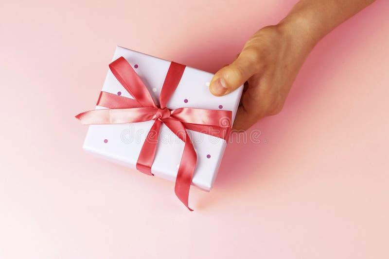 有丝带的男性手藏品礼物盒在桃红色背景,顶视图 库存图片
