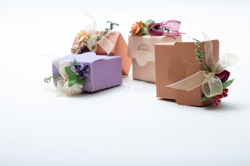 有丝带的礼物盒和在白色backgroun的人造花 库存图片