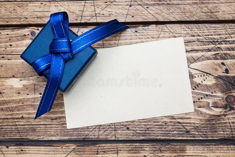 有丝带的蓝色文本的礼物盒和空间在木桌上 库存照片