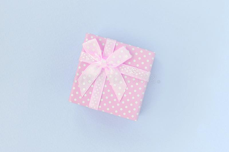 有丝带谎言的小桃红色礼物盒在紫罗兰色背景 免版税库存图片