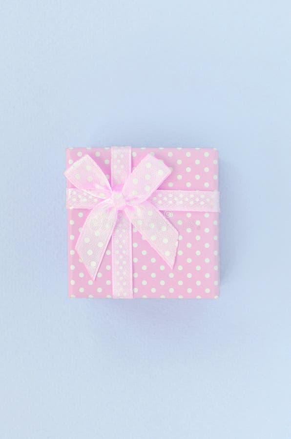 有丝带谎言的小桃红色礼物盒在紫罗兰色背景 库存图片