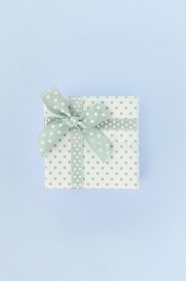 有丝带谎言的小白色礼物盒在紫罗兰色背景 免版税库存图片