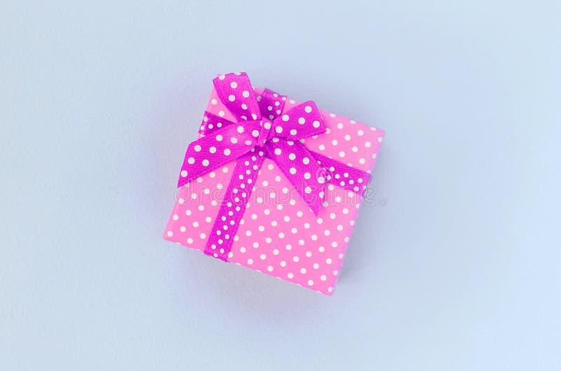 有丝带谎言的小紫色礼物盒在紫罗兰色背景 免版税图库摄影