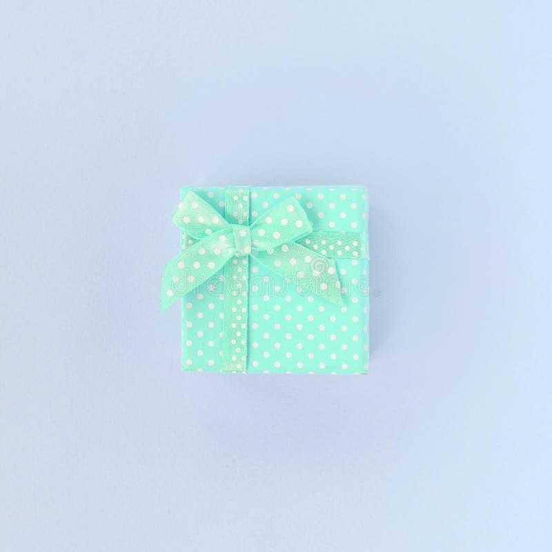 有丝带谎言的小蓝色礼物盒在紫罗兰色背景 免版税库存照片