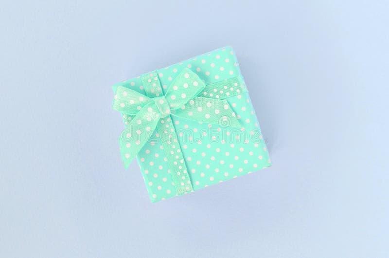 有丝带谎言的小蓝色礼物盒在紫罗兰色背景 免版税库存图片