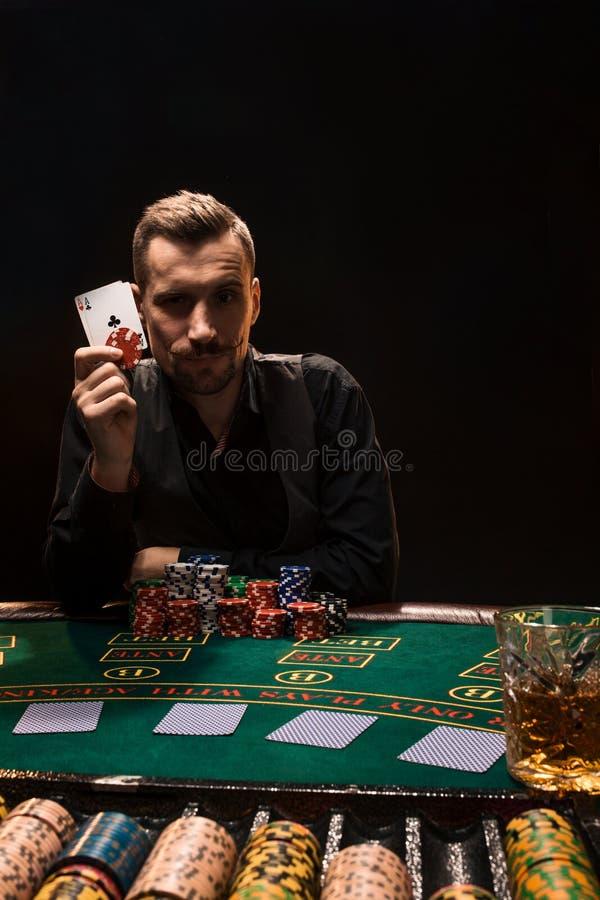 有两一点的英俊的打牌者在他的手和芯片上在啤牌桌上坐黑背景 库存图片