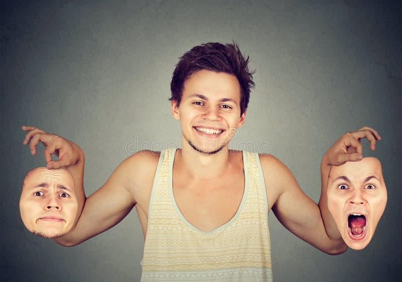 有两个不同情感面具的微笑的人 图库摄影