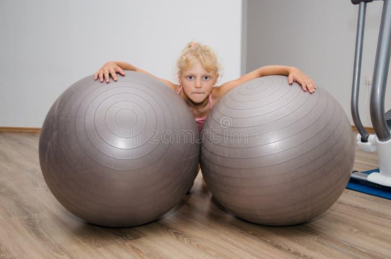 有两个健身房球的女孩 免版税库存照片